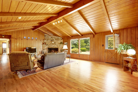 Log cabin house interior with vaulted ceiling. Living room with fireplace and leather couch Stockfoto