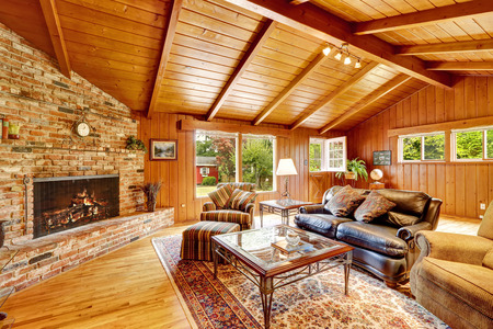 Log cabin house interior with vaulted ceiling. Luxury living room with fireplace, leather couch and glass top coffee table