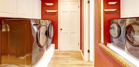 dryer  estate: Laundry room interior with brigh red walls, white cabinets and black washer and dryer