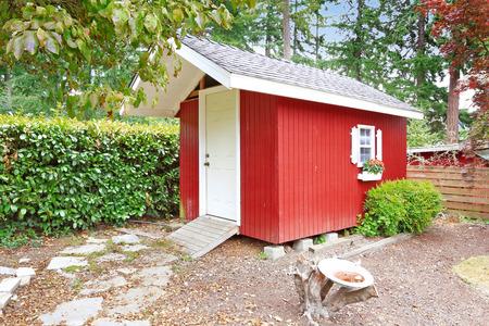裏庭の領域に明るい赤い木の小屋
