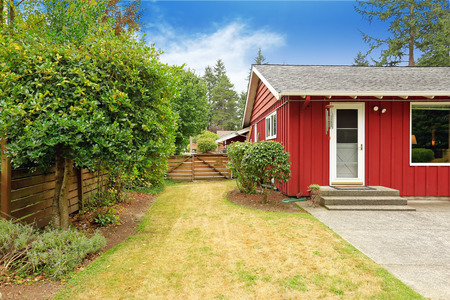 a small house: Red house exterior with walkout basement. Backyard view Stock Photo