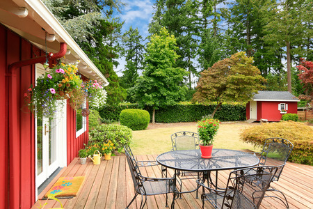 Beautiful bright red house with patio area on walkout deck and small red shed on backyard photo