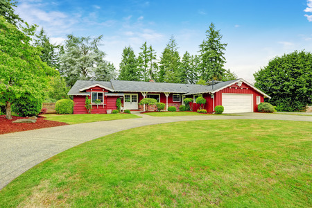 Beautiful red American classic farm house with chuge green lawn. View of entrance porch with walkway and garage with driveway