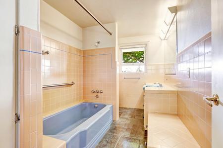 Soft ivory pink antique bathroom with light blue bath tub. Unique modern old home build in 1952. Foto de archivo
