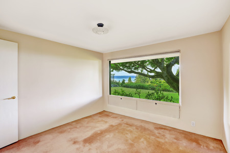 build in: Bright empty room with beautiful window view and soft pink brown carpet floor. Build in 1952. Unique old modern home.