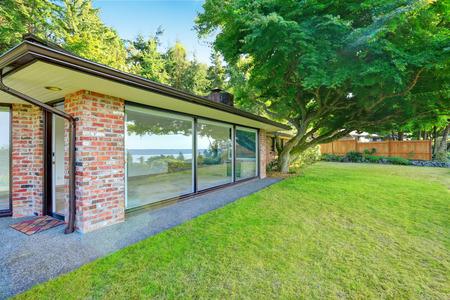 Hermosa casa de ladrillo con paredes de cristal. Patio trasero con césped y árboles marple japonés. Construir en 1952 Unique viejo hogar moderno.