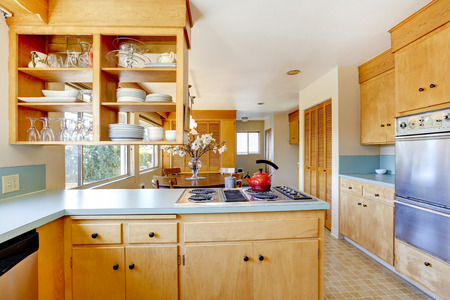 kitchen cabinets: Light tone kitchen cabinets with mint color top and built-in stove Stock Photo