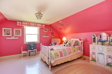 Mooie meisjes kamer in fel roze kleur met gesneden houten bed en speelgoed Stockfoto