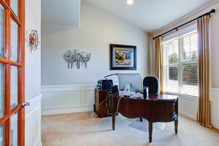 office furniture: Office room in luxury house with carved wood desk Stock Photo