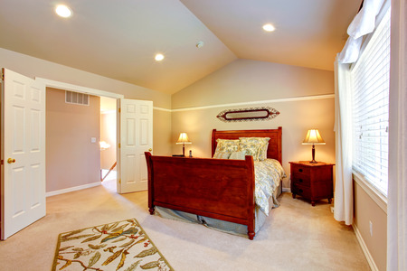 furnished: Light tones bedroom with vaulted ceiling, furnished with wood  bed.