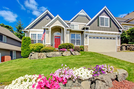 front view: Grey house exterior with entrance porch and red door. Beautiful front yard landscape with vivid flower and stones Stock Photo