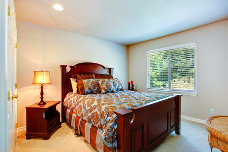 nightstands: Light tones bedroom with rich wood carved bed and nightstands Stock Photo