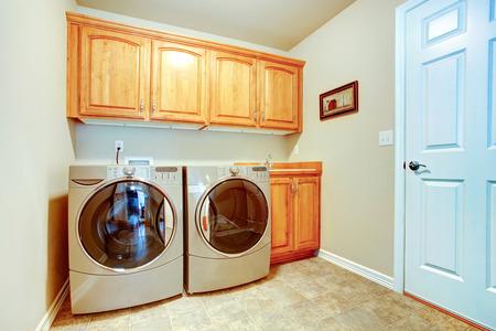Cuarto de lavado con modernos electrodomésticos y gabinetes de tonos de luz
