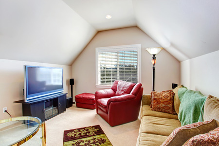 vaulted: Living room with vaulted ceiling. Furnished with bright red armchair, brown sofa and tv