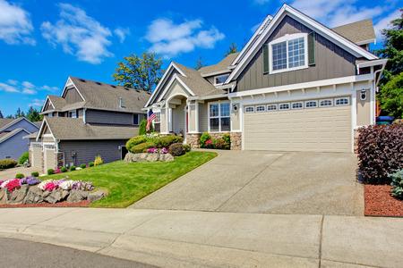 Grijs huis buitenkant met ingang veranda. Mooie voortuin landschap met levendige bloemen en stenen