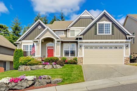 woonwijk: Grijs huis buitenkant met ingang veranda en rode deur. Mooie voortuin landschap met levendige bloemen en stenen Stockfoto
