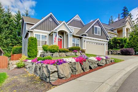 玄関ポーチと赤と灰色の家の外観。鮮やかな花と石の美しい前庭風景