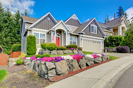 Grey house exterior with entrance porch and red door. Beautiful front yard landscape with vivid flower and stones Imagens