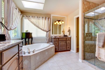 mauve: Beautiful bathroom interior in light mauve color with glass door shower and round bath tub