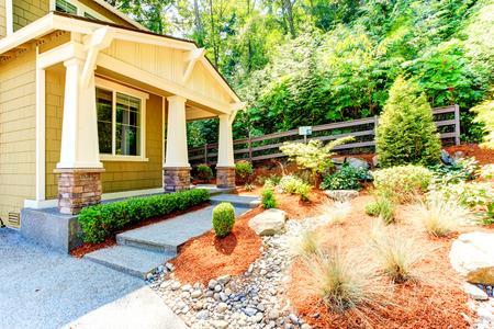 front porch: American achitecture. Walkout basement porch with columns. Stone base trim columns. Front yard landscape Stock Photo