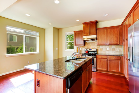 kitchen cabinets: Modern kitchen cabinets with ss-appliances and kitchen island with built-in sink and granite top Stock Photo