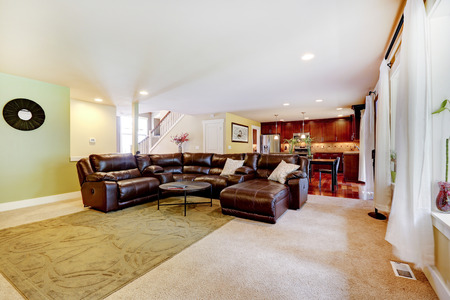 open plan: House interior with open floor plan. Living room with leather couch and kitchen area