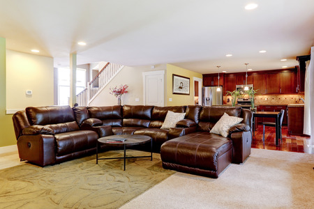 open floor plan: House interior with open floor plan. Living room with leather couch and kitchen area