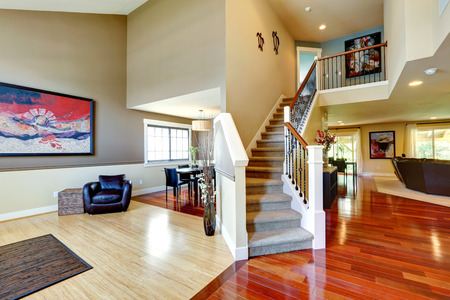 open plan: House interior. Entrance hallway with contrast hardwood floor and carpet covered staircase