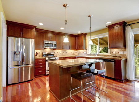 granite kitchen: Bright shiny kitchen room with granite tops, tile back splash trim and steel stainless appliances Stock Photo