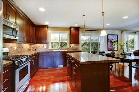 appliances: Bright shiny kitchen room with granite tops, tile back splash trim and steel stainless appliances.