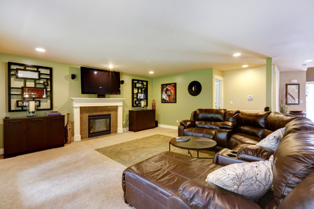 Light green living room with fireplace, TV and leather couch photo