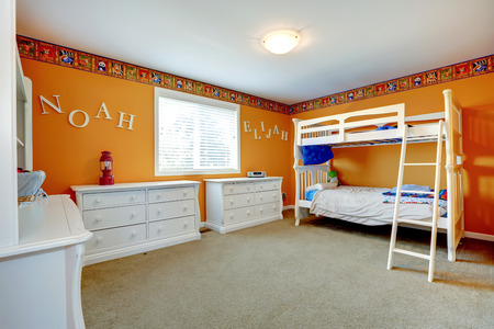 kids bedroom: Bright orange kids room with white dressers and bulk bed