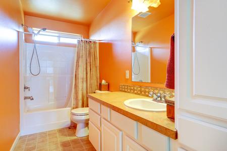 white trim: Bright orange bathroom interior with white tile wall trim