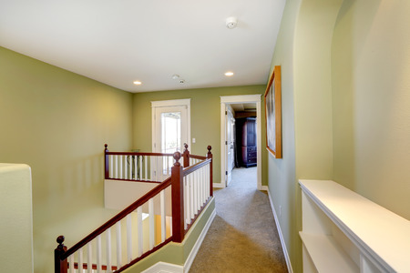 upstairs: Mint upstairs hallway with carpet floor and white railings with brown trim
