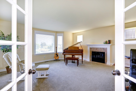 arm chair: Ivory bright room with fireplace, grand piano, guitar and chair with foot rest