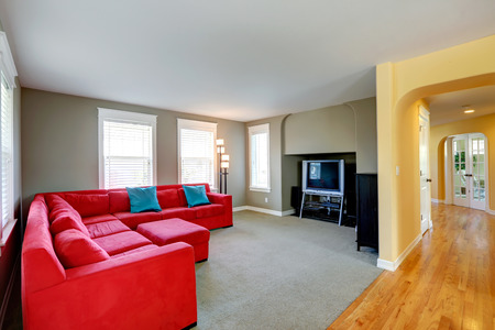 House interior. Corridor with archway and hardwood floor. Living room with bright red couch and tv photo