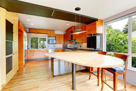 kitchen cabinets: Modern kitchen room with orange cabinets and dininig table with stools Stock Photo