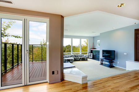 living room window: Bright house interior. Living room with large window and hallway with door to walkout deck