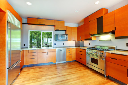 home appliances: Modern kitchen room with orange cabinets and steel appliances