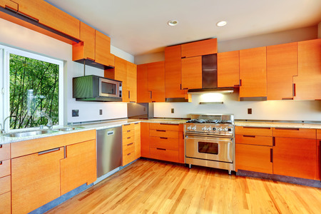 kitchen cabinets: Modern kitchen room with orange cabinets and steel appliances