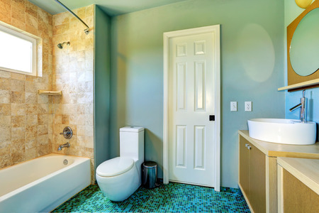 vessel sink: Light blue bathroom interior with modern vanity cabinet with vessel sink and tile wall trim
