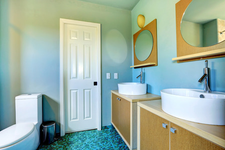 vessel sink: Light blue bathroom interior with modern vanity cabinets with vessel sinks and mirrors