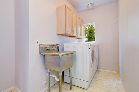 Small laundry room with whtie appliances, two cabinets and old sink photo
