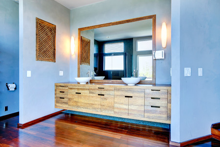 bathroom mirror: Light blue bathroom interior. View of wooden cabinet with vessel sinks and large mirror