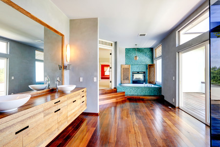 sinks: Bathroom with turquoise tile trim and fireplace. View of wooden cabinet with vessel sinks and mirror Stock Photo