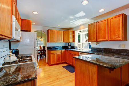 kitchen cabinets: Kitchen room with wooden cabinets and black granite tops.