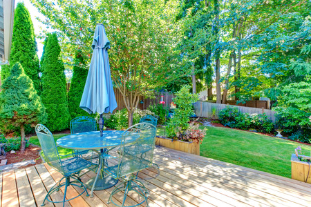 Walkout deck with patio table and umbrella overlooking backyard gaden