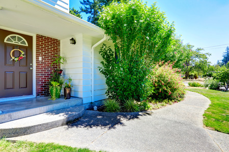 front porch: American architecture. House with brick wall trim. View of small entrance porch with flower pots Stock Photo