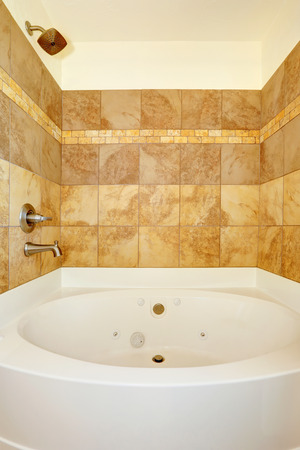 white trim: Ivory tile wall trim in bathroom with white whirlpool tub Stock Photo