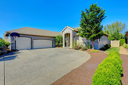 curb appeal: Modern house exteior with entrance porch. View of garage with driveway and flower bed Stock Photo